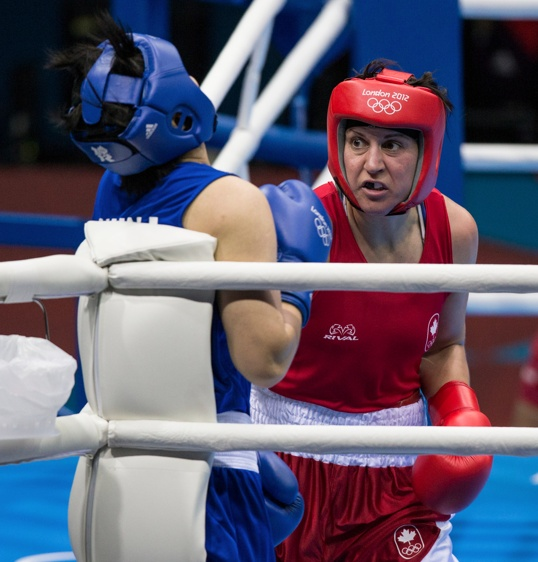 Canada's Mary Spencer puts Jinzi Li of China on the ropes during a middleweight boxing quarter-final at the 2012 London Olympic Games, August 6, 2012. Spencer lost the fight 17 to 14 and is out of the competition.  COC Photo: Jason Ransom
