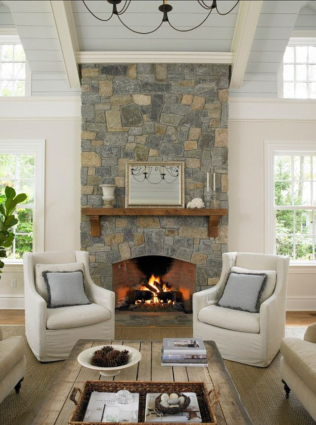Pretty stone fireplace with a chunky wood mantle, light walls, and pale blue paneled ceiling