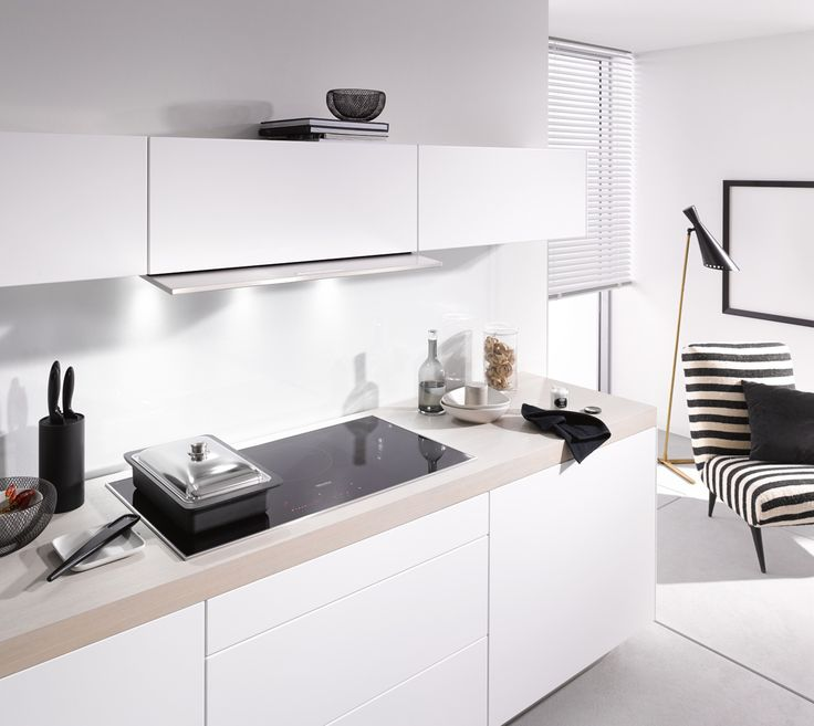This monochrome kitchen is completed with sleek white handleless cupboards and Miele's DA3690 integrated cooker hood
