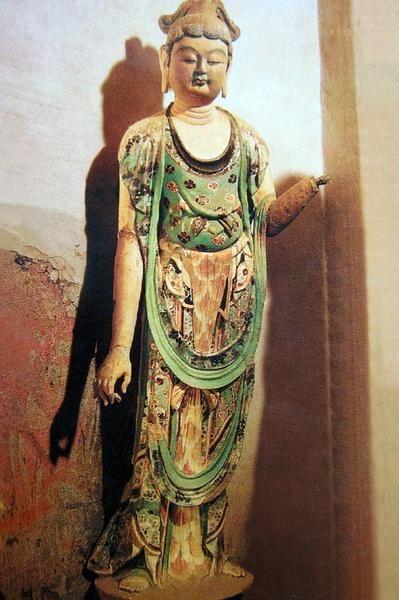 菩薩,敦煌第194窟,盛唐,立於蓮台上的菩薩像,位於佛的右側,高1.42米。頭梳垂雙環髻,面頰豐腴,兩目低垂,穿圓領無袖上衣,披巾回繞,搭於左肘。衣裙上彩繪花朵,富有絲綢織繡質感,神情嫺靜,姿態嫵媚,宛若貴族少婦形象。