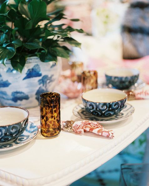 Jamie Meares Photo - A white dining table set with tortoiseshell glasses and blue dishes