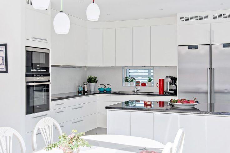 Vitt, slätt kök med gott om arbetsytor och förvaring. Bänkskiva i svart granit och maskiner i rostfritt. En köksö bidrar till extra arbetsytor och social matlagning | Ballingslöv