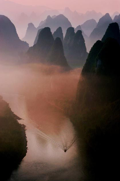 A boat passing through the mountains.  Guilin, Guangzhou, China. Photo by Ted Lee