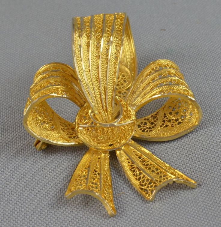 Vintage Gold Plated Sterling Silver Filigree Floral Ribbon Bow Shaped Pin Brooch ca.1930-1940 | eBay (The seller doesn't mention its provenance, but this kind of work is most likely from Portugal, and the fact that this is .925 sterling makes me believe it even more. Portuguese silver is .925 by standard, and I remember seeing pieces like that in jeweler shops many years ago. Great pieces like this are usually gold plated)