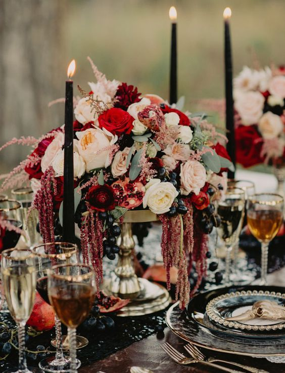 36 Ideas To Throw A Halloween Wedding With Style: #4. Very lush flower and grapes centerpiece with black candles and a black table runner