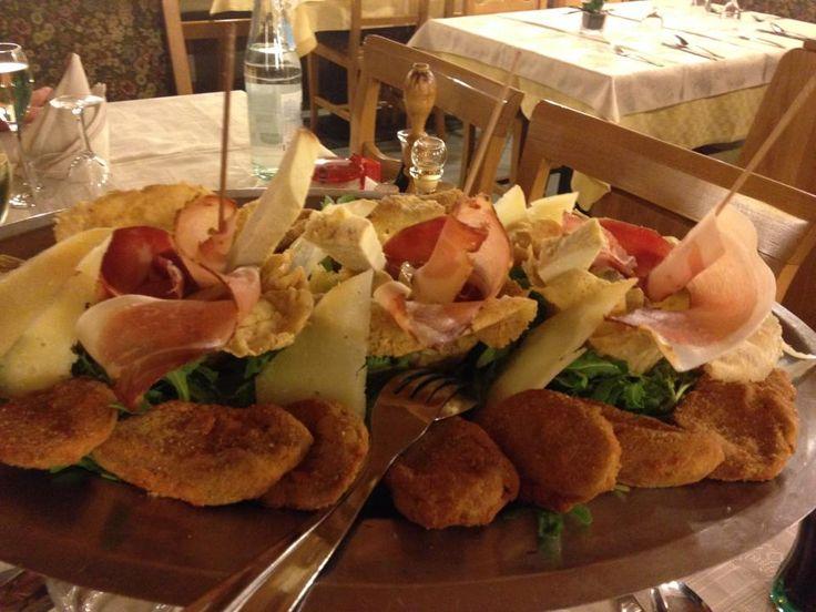 estiuni di frico con porcini, spek e ricotta affumicata, circondati da funghi fritti panati