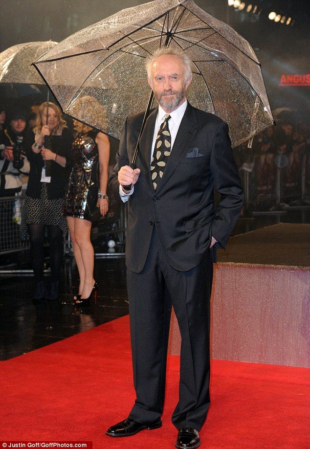 Umbrellas at the ready: Actor Jonathan Pryce also tried to keep dry in the winter weather