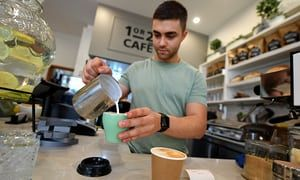 A barista is seen preparing a coffee at a cafe in Canberra