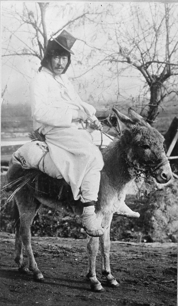 A man rides a donkey in front of a barren landscape and wears a traditional Korean hat called a gat. Typically made from horsehair and bamboo, these hats date from the Choson dynasty before the Japanese occupation and were traditionally worn to signify rank.