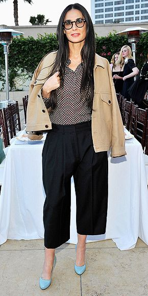 DEMI MOORE in a tan jacket draped over her printed button-down, plus culottes and baby blue shoes at a dinner hosted by shoe designer Charlotte Olympia Dellal and filmmaker Liz Goldwyn in West Hollywood, California.