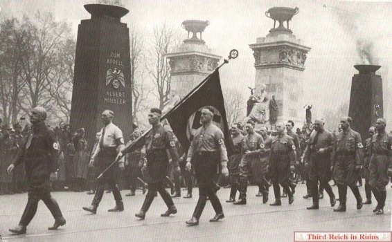 Julius Streicher led the march, followed by Jakob Grimminger with the Blutfahne. The entire route was lined by tall red pylons with torch bowls on the top, ...