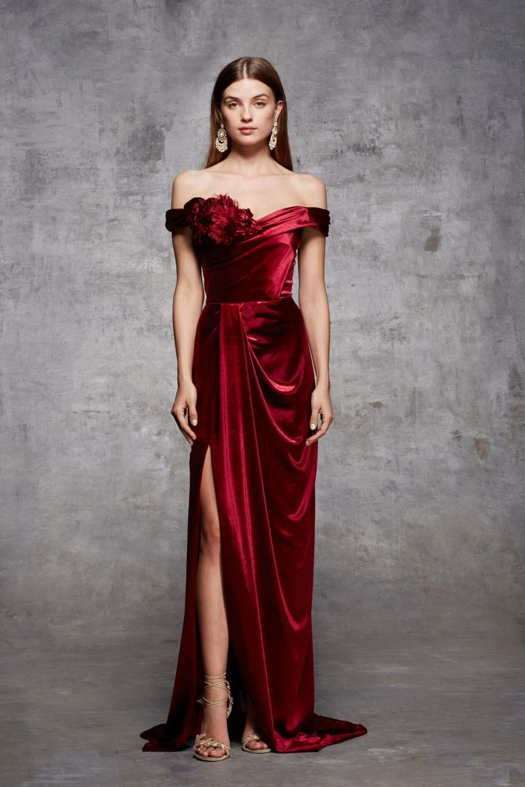 Off shoulder velvet column gown with corseted draped bodice, high slit at front skirt and 3D stamped velvet and satin faced organza flower corsage at neckline