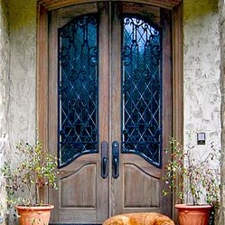 This door is a pair of Double Distressed Cypress Doors with custom Wrought Iron Grills over Decorative Leaded glass.