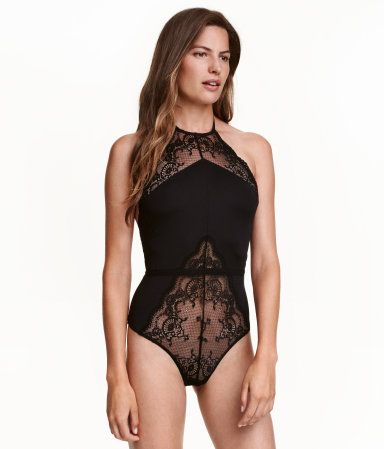 Black. Halterneck bodysuit in microfiber with lace sections. Low-cut back, tie at back of neck, and elasticized seam at waist. Lined gusset with snap