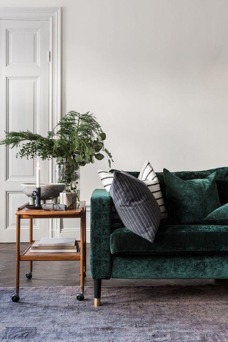 luxe green velvet sofa | retro bar cart sideboard | fir tree and eucalyptus bouquet | IKEA Karlstad sofa with a Bemz cover in Viridian velvet by Designers Guild | Bemz cushion covers | panelled wooden door | herringbone floors
