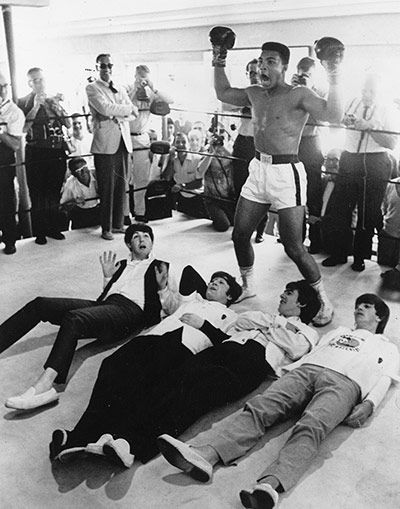 Muhammad Ali (then Cassius Clay) poses in mock victory over The Beatles...