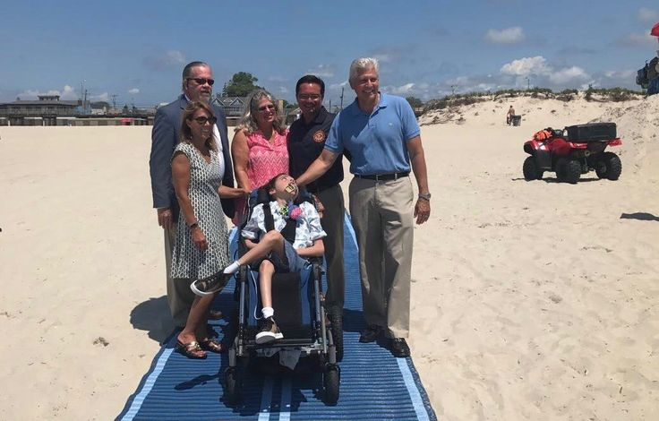 The mobility mat stretches from an entrance pathway to nearly the shoreline for easier access to the beach. Above from left were, Matthew Dwyer of the Nassau County Office for the Physically Challenged, Assemblywoman Melissa Miller, Atlantic Beach Trustee Linda Baessler, Oliver Miller, Mayor George Pappas and Councilman Bruce Blakeman.