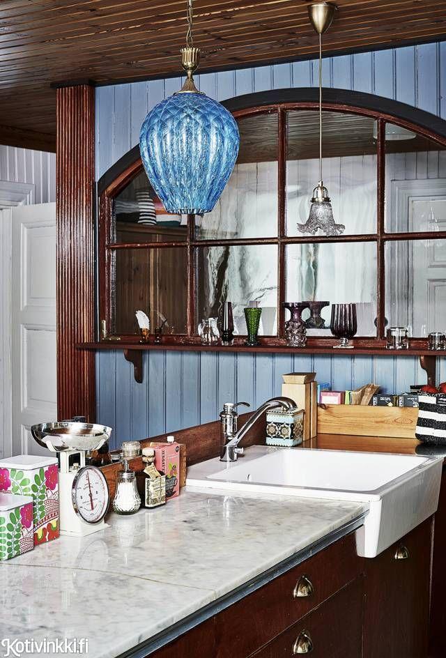 Koti vanhassa kaupassa. Sininen Murano-lasinen valaisin on kirpputorilöytö. Keittiön väliseinä rakennettiin suuren ikkunan raameiksi. Keittiön uudistuksen suunnitteli ja teki lyhytelokuvaohjaaja Juhana Manner.
