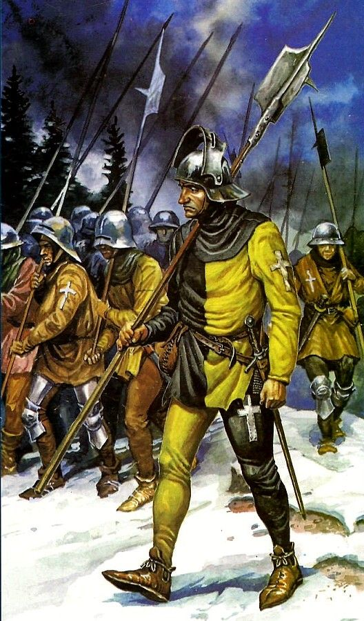 A man of the Swiss infantry. Dressed in Yellow and black, his attire is differed from others as the colours are split down the middle. The soldiers behind him aren't wearing the same pattern of colours, most of them are wearing leather armour.