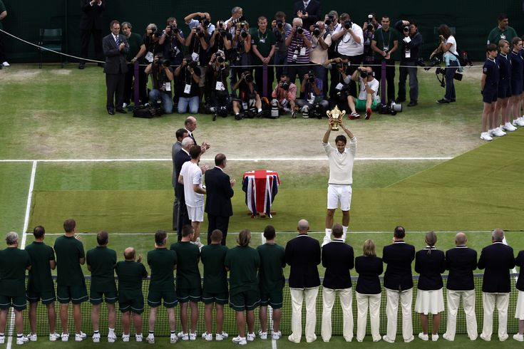 Roger Federer raises the championship trophy after defeating Andy Murray and claiming his seventh Wimbledon title. - Tommy Hindley/AELTC