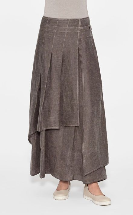 A layered illusion. This paneled skirt creates an intricate pleated aesthetic. Its asymmetrical effect and coated-linen design add some texture to your routine. To complement the style, wear the long skirt with a fitted short sweater or a T-shirt and wedges.