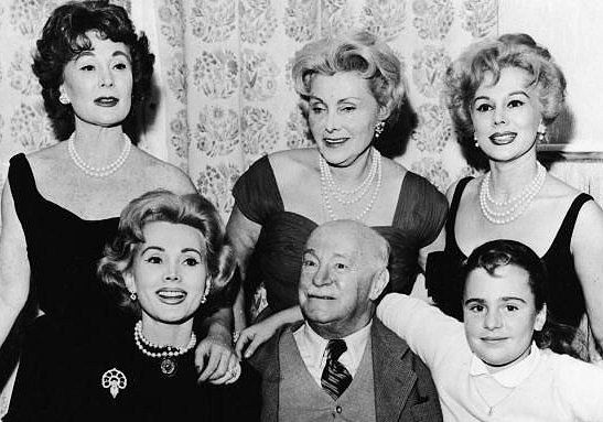 Three generations of Gabors gather in the Hotel Sacher, Vienna, Austria, circa 1955. Left to right: (top row) Magda (1919 - 1997), Mama-Jolie Gabor (1894 - 1997 - married three times herself) and Eva Gabor (1917 - 1995); (bottom row) Zsa Zsa (1917 and still going!) and Papa Gabor (1884 - 1962) and Francesca Hilton, age 8, Zsa Zsa's daughter by hotel magnate Conrad Hilton. Francesca is the only child to result from the combined 20 marriages of the three Gabor sisters.