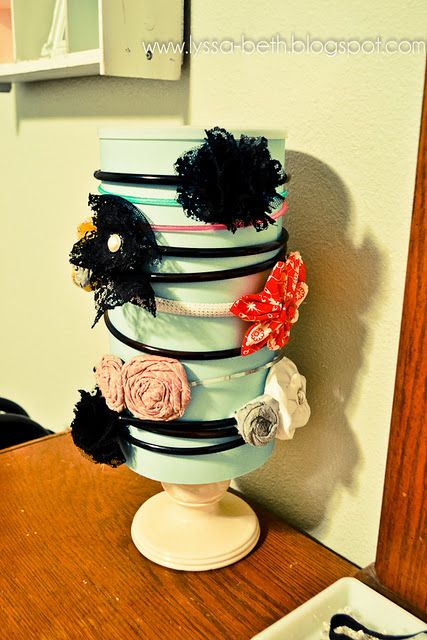 Headband organizer made with an oatmeal can, some paper, and an old candle holder.  Elastics, brushes, and other hair accessories go inside.