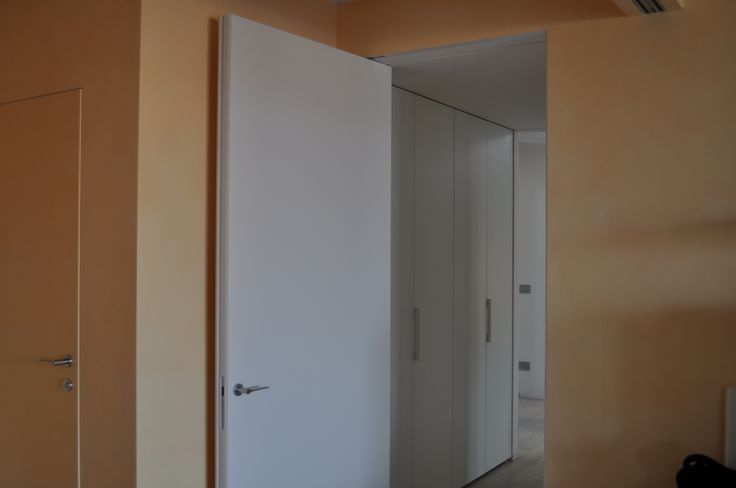 Linvisibile Vertical Pivot door. Project by Alberto Ferraresi architect. Renovated attic with doors painted as the wall.