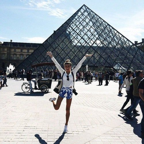 Chica saltando frente al museo de Luvre en Paris