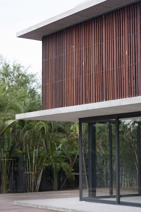 Slatted timber screens shade poolside residence in Thailand by Architectkidd.