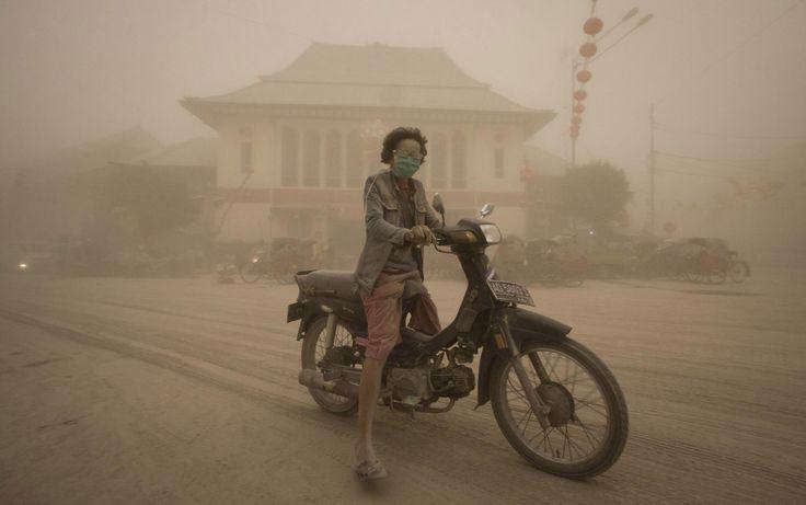 Mulher guia moto em uma rua coberta de cinzas vulcânicas da erupção do Monte Kelud, em Solo, Indonésia.