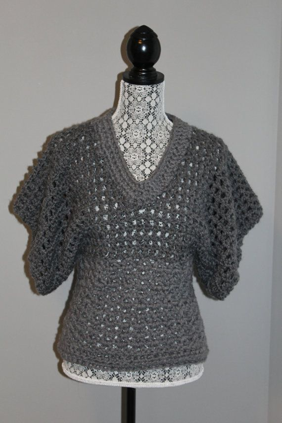 This sweater is hand-crocheted with medium grey soft yarn. The short sleeves are great for wear over a long-sleeved t-shirt. Size is