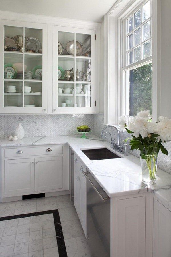 The Backsplash Tile Is A Carrara Bianco Herringbone Elegant Kitchen With Gl Front Cabinets Stainless Steel Liances Marble Countertops
