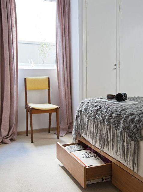 Dormitorio principal de un departamento con cama de petiribí y cajones debajo del elástico; silla escandinava tapizada en lino color maíz y ventana con cortinas largas en rosa.