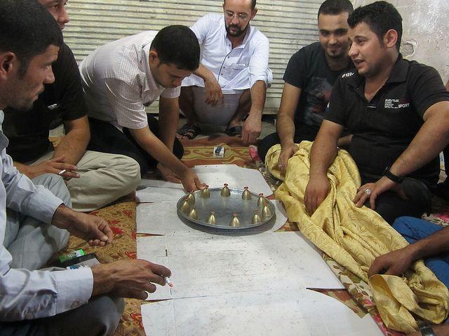 """Dos equipos rivales tratan de encontrar la aceituna bajo una de las 11 copas sobre una bandeja, un juego tradicional que se practica únicamente durante el mes sagrado musulmán de Ramadán. Pero en esta ciudad iraquí constituye todo un desafío a la muerte. """"Cruzamos nuestros vehículos al final de la calle para evitar que se estacionen coches bomba. También hay policías de civil entre nosotros"""", explica Haukar, el dueño de un cafetín en Sorja, barrio"""