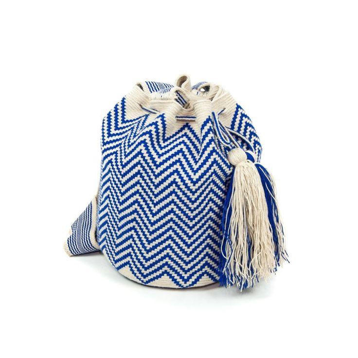 Colores:   Tejido a mano en Crochet. Asa trenzada Bolso Wayuu Beige con tonos azul. Medidas aproximadas:        - Alto: 25 cm       - Cinta: 106 cm       - Diámetro: 25cm  Cada bolso está hecho a mano, por tanto es una pieza única. El diseño puede variar ligeramente.