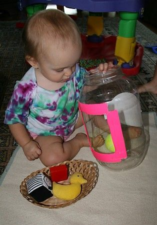 Putting objects in a large container. Independent play to keep baby busy.