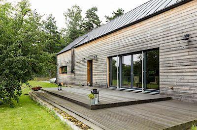 Dům je obložen předsazenou dřevěnou fasádou ze sibiřského modřínu.