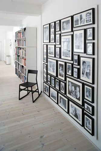 A variety of family photos framed in the same black style with white mats, creating a striking gallery wall http://www.thebooandtheboy.com/2011/02/family-photos-on-display.html