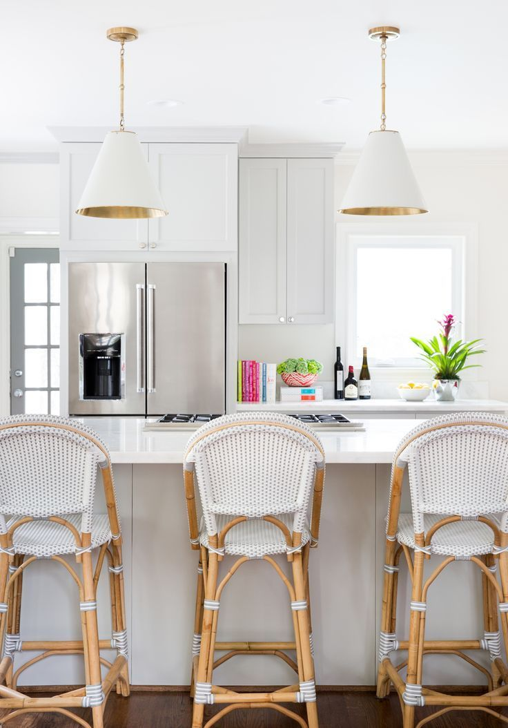 White kitchen with Serena & Lily's Goodman Pendant and Riviera Counter Stools | Image via J Barron Interiors