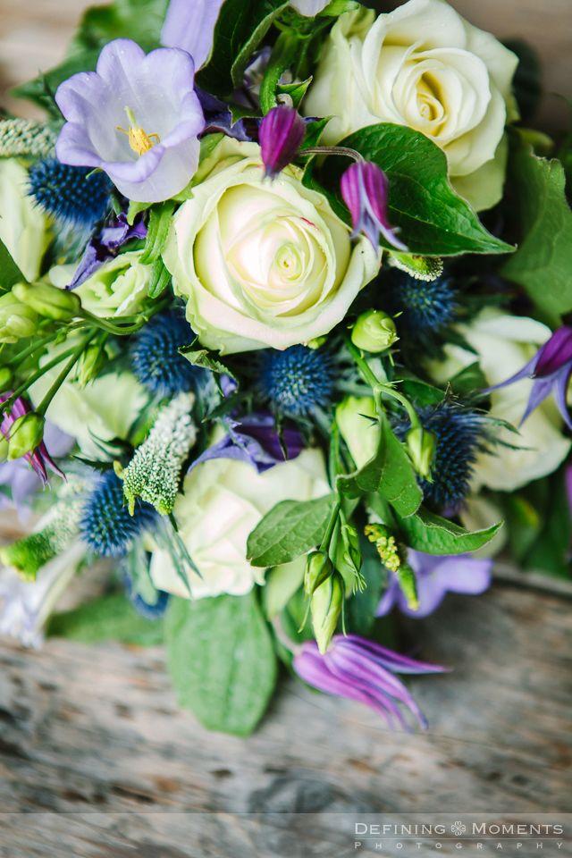 Bruidsboeket in paars, blauw, crème en zachtgroene tinten. Witte rozen, lila campanula's, blauwe distel en fris groen.