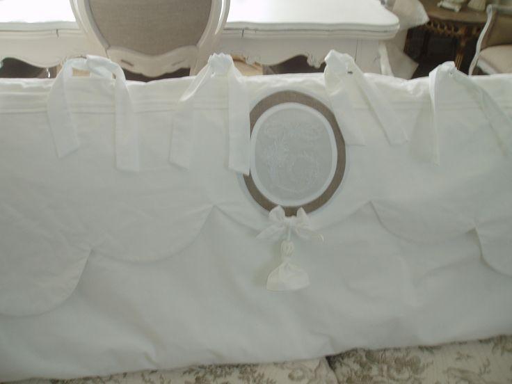 Tête de lit . En linge ancien. Cantonnière festonnée, réhaussée d'un monogramme en médaillon et d'un pompon