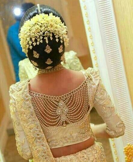 What a beautiful large low bun with gajra & juda pins! Care however should be taken before adopting such hairstyles, as due to it's high static charge, it will cause phlegm to move up in the throat, causing the voice to quaver & a frequent urge to clear the throat. A heavy chabi chhalla with a long & wide hook if inserted at the edge of the pleats of the saree, will reduce this problem as it's hook will activate the acupressure points that act to keep the throat clear.
