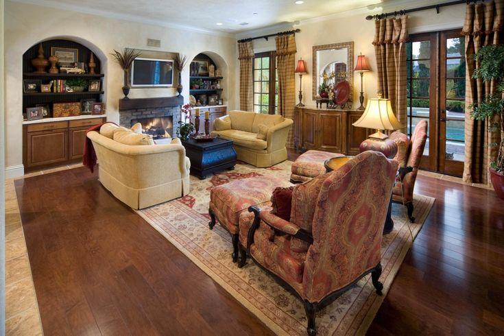 This Tuscan style family room has a reclaimed timber mantel, hand knotted rug and oversized furnishings. The warm color palette makes this space feel comfortable and inviting.
