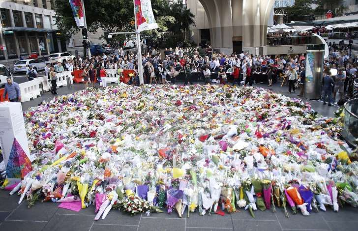 Flowers are placed by people as a mark of respect for the victims of Martin Place siege.