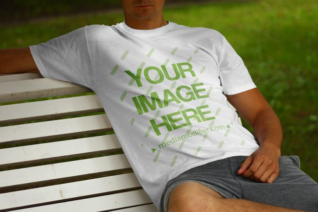 Online mockup scene with a young white male model sitting on a park bench in summertime. Upload your own custom design on the blank round neck shirt and generate a preview within seconds. Online t-shirt front view mockup generator with a young man sitting and resting in the park.