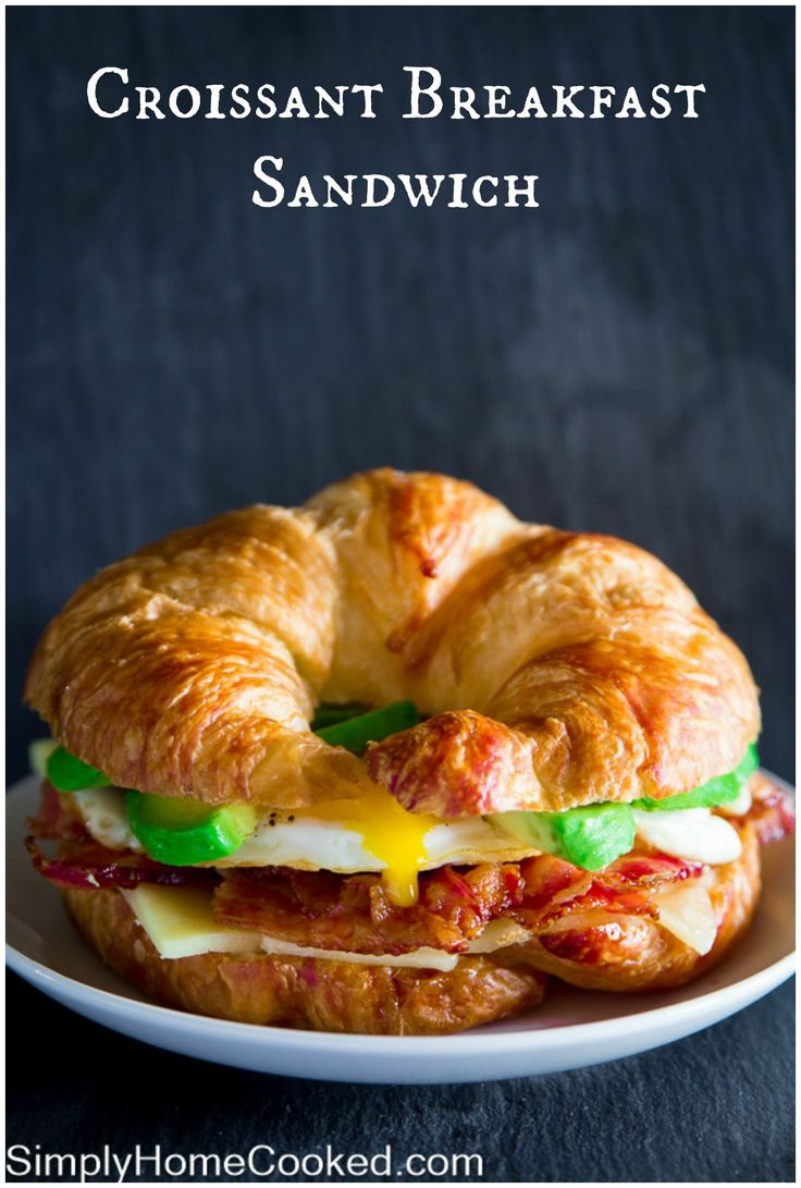 Croissant breakfast sandwich loaded with crispy bacon, white cheddar, avocado…