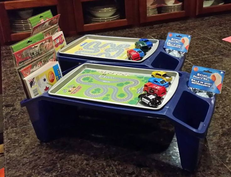 "From my friend, Hillary Dorksen: I got the blue tray part at walmart and filled the side pockets with coloring books, crayons, etc. from the dollar store (and I'll put snacks in there too). I got dollar store cookie sheets and added magnets to the bottom of the cars so they'll stick. I printed out car tracks (Google ""race track rug"") and laminated them then put strip magnets on the back of the track pictures so they'll stick to the cookie sheets. Each setup was about $12."