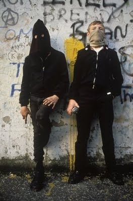 Two young Óglaigh na Héireann urban guerrillas with petrol bombs prepare to clash with Her Majesty's occupational forces. (Homer Sykes, 1980)