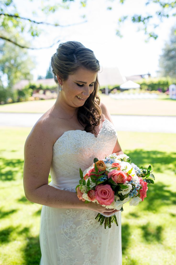 Coral garden roses, coral ranunculus, white roses, blue tweedia bridal bouquet. Summer wedding at Columbia Edgewater Country Club, Portland, Oregon. Photo courtesy of Powers Photography